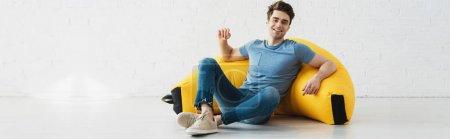 Photo pour Plan panoramique de l'homme heureux assis près de chaise sac haricot jaune à la maison - image libre de droit