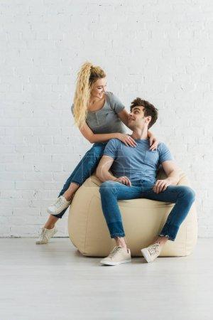 Foto de Hombre feliz mirando a la chica rubia alegre mientras se sienta en la silla de bolsa de frijoles beige en casa - Imagen libre de derechos