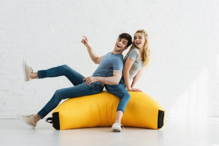 cheerful blonde girl and happy man sitting on yellow bean bag chair