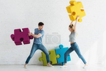Photo pour Femme gaie et homme heureux se battant avec des pièces de puzzle à la maison - image libre de droit