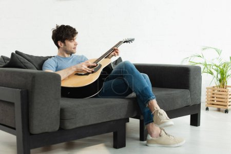 Photo pour Handsome man sitting on sofa and playing acoustic guitar at home - image libre de droit