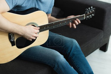 Photo pour Cropped view of man sitting on sofa and playing acoustic guitar at home - image libre de droit