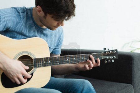Photo for Handsome musician playing acoustic guitar while sitting on sofa at home - Royalty Free Image