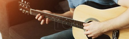 Photo pour Panoramic shot of musician playing acoustic guitar at home - image libre de droit