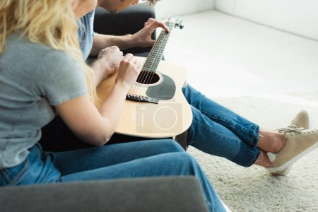 Photo for Cropped view of man playing acoustic guitar near blonde woman sitting on sofa - Royalty Free Image