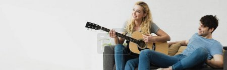 Photo for Panoramic shot of happy blonde girl playing acoustic guitar  near man - Royalty Free Image