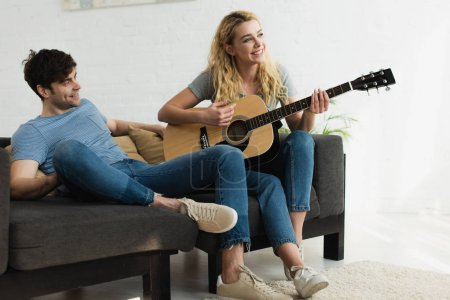 Photo for Happy blonde girl playing acoustic guitar near cheerful man - Royalty Free Image