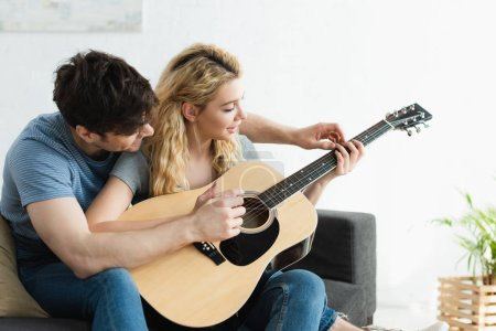 Photo for Handsome man teaching blonde happy woman playing acoustic guitar at home - Royalty Free Image