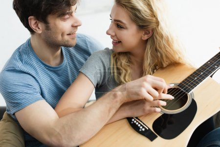 Photo for Happy man and cheerful blonde woman holding hands of strings and looking at each other - Royalty Free Image