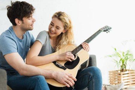 Photo pour Happy blonde woman holding acoustic guitar near cheerful man sitting on sofa - image libre de droit