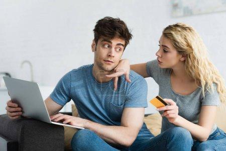 Photo pour Femme blonde pointant du doigt vers un ordinateur portable près d'un homme tenant une carte de crédit - image libre de droit
