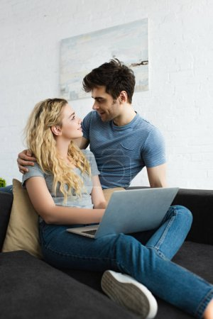 Photo pour Bel homme étreignant et regardant heureuse fille blonde avec ordinateur portable - image libre de droit