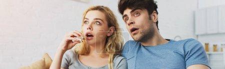 panoramic shot of shocked man watching movie near blonde girl holding popcorn