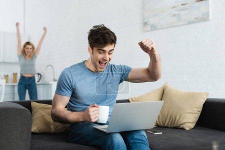 Photo pour Foyer sélectif de l'homme heureux célébrant le triomphe tout en regardant le championnat sur ordinateur portable près de la femme - image libre de droit
