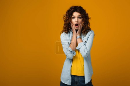 Photo for Surprised redhead woman looking at camera and touching face on orange - Royalty Free Image