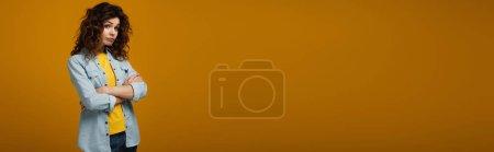 Photo pour Tir panoramique de la femme rousse bouclée bouleversée regardant l'appareil-photo et restant avec les bras croisés sur l'orange - image libre de droit