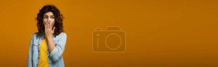 Photo pour Tir panoramique de la femme de rousse étonnée couvrant la bouche tout en restant sur l'orange - image libre de droit