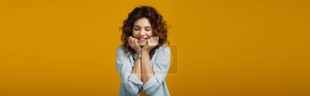 Photo for Panoramic shot of pretty cheerful redhead woman smiling with closed eyes on orange - Royalty Free Image