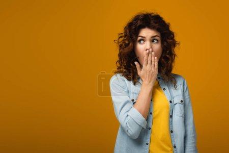 Foto de Mujer pelirroja sorprendida cubriendo la boca mientras está de pie en naranja - Imagen libre de derechos