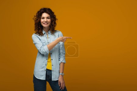 Photo for Cheerful curly redhead woman standing and pointing with finger on orange - Royalty Free Image