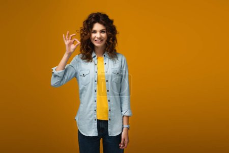 Photo for Cheerful curly redhead woman standing and showing ok sign on orange - Royalty Free Image