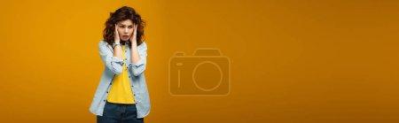 Photo pour Plan panoramique de femme bouclée bouleversée touchant la tête tout en ayant la migraine sur orange - image libre de droit