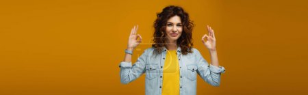 Photo for Panoramic shot of cheerful curly redhead woman standing and showing ok signs on orange - Royalty Free Image