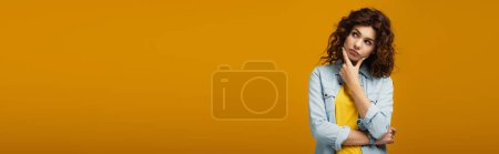 Photo for Panoramic shot of pensive woman thinking while standing on orange - Royalty Free Image