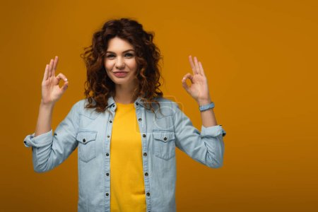 Photo for Cheerful curly redhead woman standing and showing ok signs on orange - Royalty Free Image