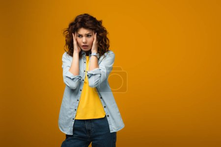 Photo for Upset curly woman touching head while having migraine on orange - Royalty Free Image
