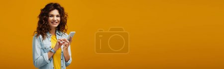 Photo pour Plan panoramique de jolie rousse bouclée femme tenant smartphone sur orange - image libre de droit