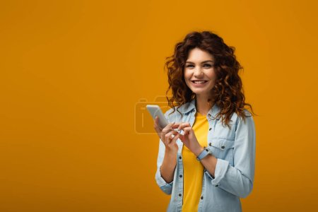 Photo pour Happy curly redhead woman holding smartphone on orange - image libre de droit