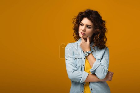 Photo for Pensive curly redhead woman touching lips while thinking on orange - Royalty Free Image