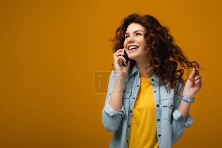 Photo for Happy curly redhead woman talking on smartphone and touching hair on orange - Royalty Free Image