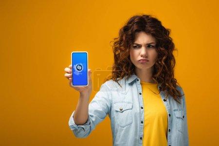 Photo for Upset redhead woman holding smartphone with shazam app on screen on orange - Royalty Free Image