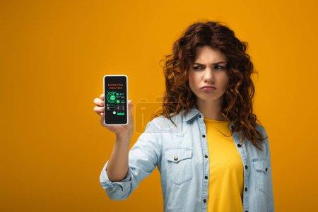 Foto de Upset redhead woman holding smartphone with marketing analysis on screen on orange - Imagen libre de derechos