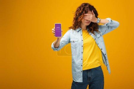 Photo pour Femme rousse couvrant des yeux et retenant le smartphone avec l'application d'Instagram sur l'écran sur l'orange - image libre de droit