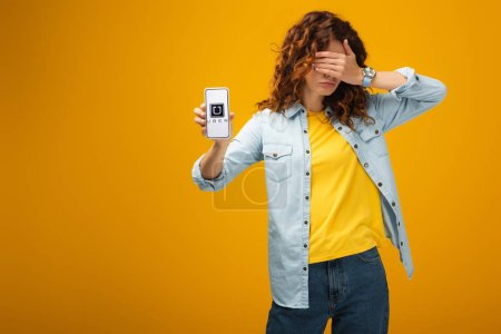 Photo for Redhead woman covering eyes and holding smartphone with uber app on screen on orange - Royalty Free Image