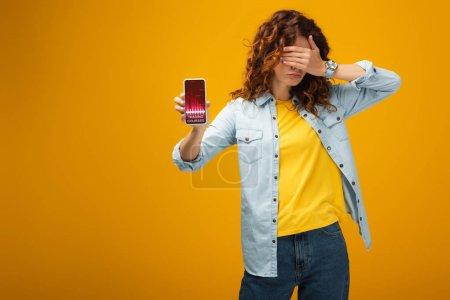 Foto de Pelirroja mujer cubriendo los ojos y sosteniendo el teléfono inteligente con cursos de comercio en la pantalla en naranja - Imagen libre de derechos