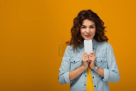 Photo for Happy redhead woman holding smartphone and smiling on orange - Royalty Free Image
