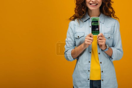 Photo for Cropped view of cheerful curly woman holding smartphone with booking app on screen on orange - Royalty Free Image