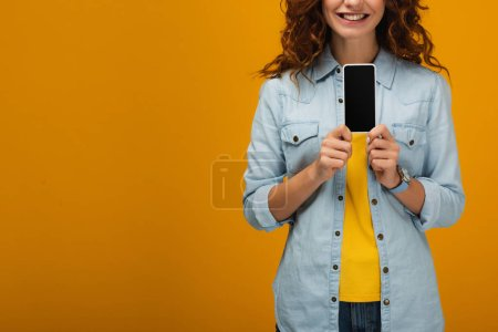 Photo for Cropped view of cheerful curly woman holding smartphone with blank screen on orange - Royalty Free Image