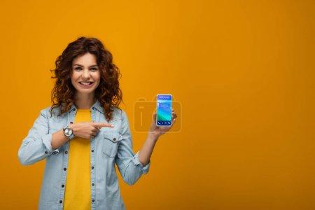 Photo pour Joyeuse rousse bouclée femme pointant du doigt le smartphone avec application de réservation à l'écran sur orange - image libre de droit