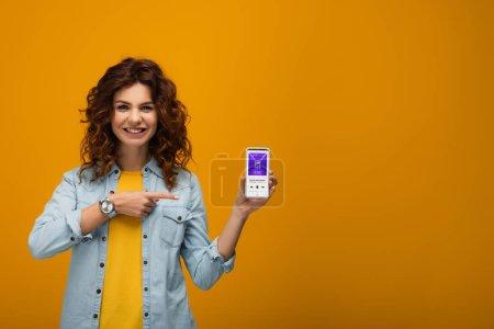 Photo pour Femme rousse bouclée gaie pointant avec le doigt au smartphone avec l'application de itunes sur l'écran sur l'orange - image libre de droit