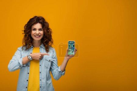 Photo pour Joyeuse rousse bouclée femme pointant du doigt à l'iphone sur orange - image libre de droit