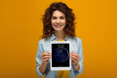 Photo for Cheerful redhead woman holding digital tablet with lock screen while standing on orange - Royalty Free Image