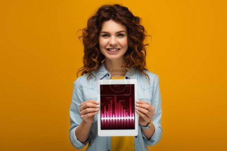 Photo for Cheerful redhead woman holding digital tablet with charts and graphs on screen while standing on orange - Royalty Free Image