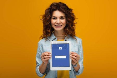 Photo pour Femme heureuse de rousse retenant la tablette numérique avec l'application de facebook à l'écran tout en restant sur l'orange - image libre de droit