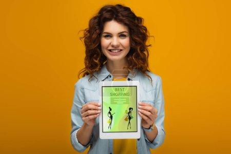 Photo pour Femme heureuse de rousse retenant la tablette numérique avec la meilleure application d'achats sur l'écran tout en restant sur l'orange - image libre de droit
