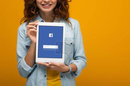 abgeschnittene Ansicht von fröhlichen lockigen Mädchen mit digitalem Tablet mit Facebook-App auf dem Bildschirm isoliert auf orange